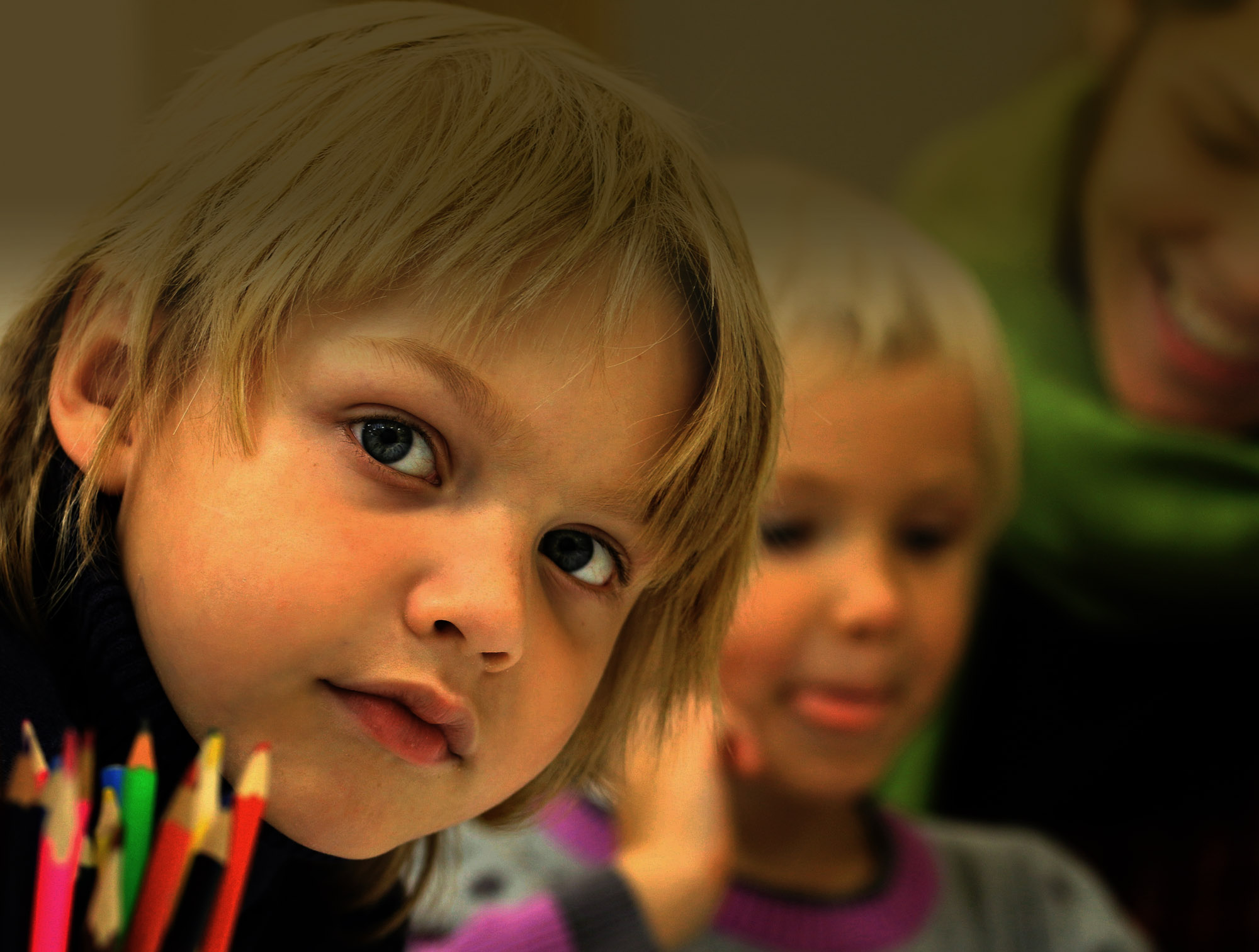 A boy looking over a set of color pencils. In the background are another child and a woman.